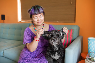 Mid adult woman sitting on sofa with dog, holding dog's ears