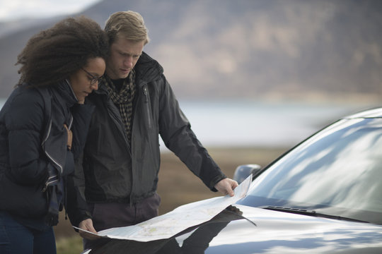 Mid adult couple by car with map