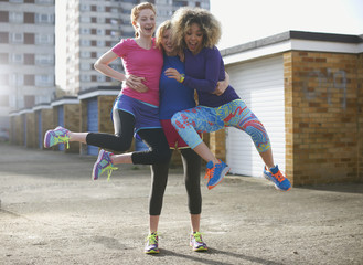 Cheerful women in sports clothing jumping outdoors