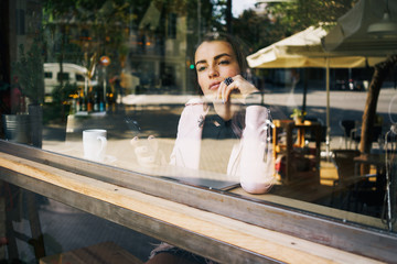 beautiful thoughtful girl thinking about something while looking out the window a cozy cafe. portrait of a cute girl who is drinking coffee near the panoramic window and holding a smart-phone in hand.