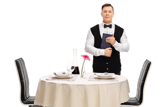 Waiter holding a menu next to a table
