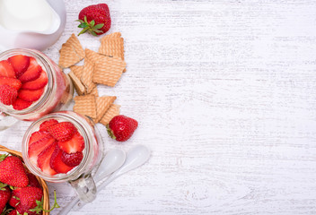 Layered dessert with strawberry and cream cheese in glass jar. Cheesecake.