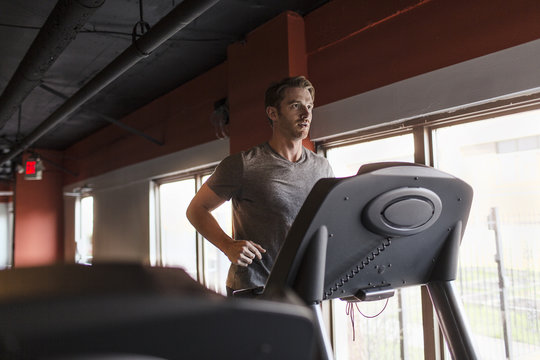 Exhausted mid adult man running on gym treadmill