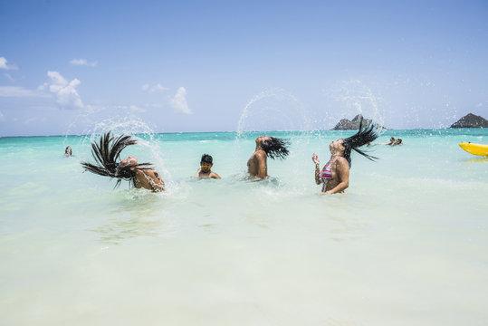 Side view of young women throwing long wet hair back in sea at Lanikai Beach, Oahu, Hawaii, USA