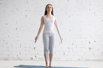 Attractive fit young woman doing Mountain pose in white loft Fototapete