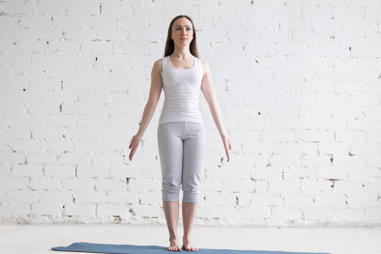 Attractive fit young woman doing Mountain pose in white loft