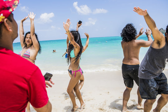 Young adult friends dancing on Lanikai Beach, Oahu, Hawaii, USA
