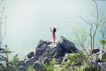 Mid adult woman, standing on rock beside lake, in yoga position, rear view