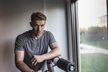 Portrait of sweaty mid adult man leaning on exercise machine in gym