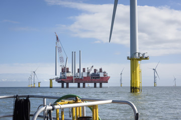 View from boat of offshore wind farm and construction ship