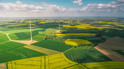 Aerial view of wind mills, flowery meadows, green fields and village, country side on a sunny and cloudy summer  day. Green energy in use. Countryside near Frankfurt, Germany.