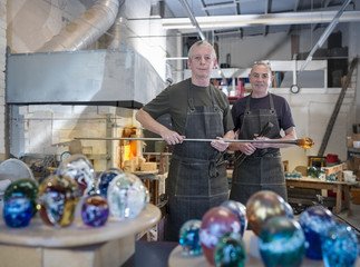 Artisan glassblowers in workshop with furnace and finished glassware