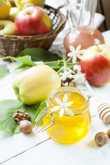 Apple and honey, traditional food of jewish New Year - Rosh Hashana, with spices, flowers and nuts on light wooden table