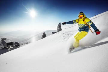 Snowboarder rides over fresh powder on the slope. Sheregesh resort, Siberia, Russia