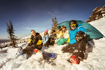 Group of friends snowboarders and skiers relaxing in camp near tent  on the slope of ski resort Sheregesh. Siberia, Russia