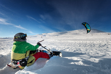 Snowboarder with kite on free ride. Sheregesh resort, Siberia, Russia