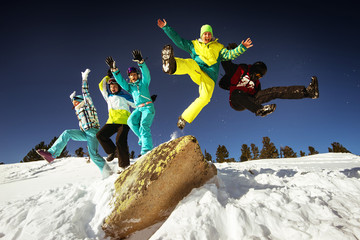 Group of happy friends having fun jumping from big rock to snow. Ski and snowboard resort Sheregesh, Siberia, Russia