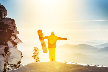 Snowboarder stands on background of valley and holds snowboard in raised hands. Sheregesh resort, Siberia, Russia