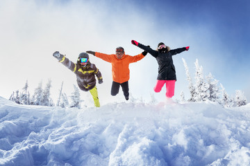 Group of three friends jumps like superhero into snowdrift. Sheregesh resort, Siberia Russia