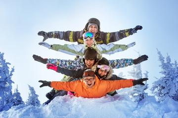Group of happy friends having fun lying on snowdrift. Sheregesh resort, Siberia, Russia