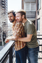 Male couple standing on balcony, looking at view, embracing