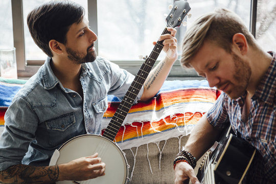 Male couple at home, play guitar and banjo