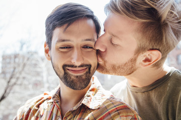 Portrait of male couple, mid adult man kissing his partner's cheek