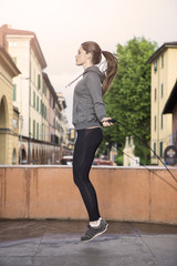 Side view of woman wearing sports clothes using skipping rope