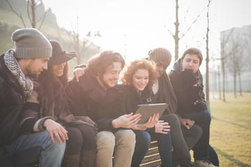 Six young adult friends reading digital tablet on park bench