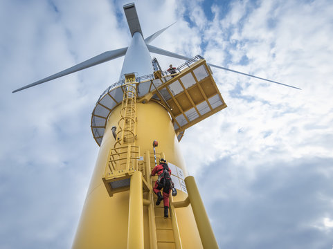Engineers climbing wind turbine from boat at offshore windfarm, low angle view