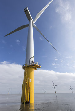 Engineer climbing wind turbine from boat at offshore windfarm