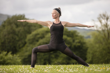 Mature woman practicing yoga reversed warrior pose with arms open in field