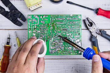 Serviceman soldering circuit board with soldering iron in the se