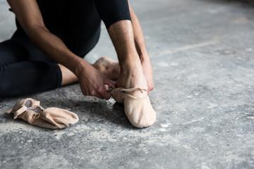 Dancer wearing ballet shoe in studio