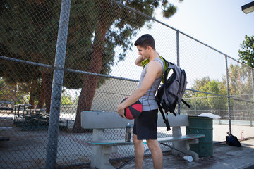 Young male basketball player preparing to leave basketball court