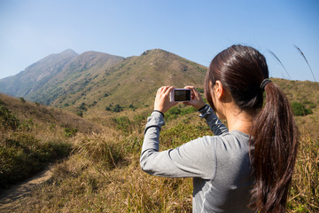 Woman taking pictures during hiking trip