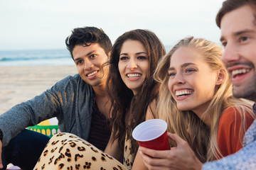 Group of friends sitting together on beach