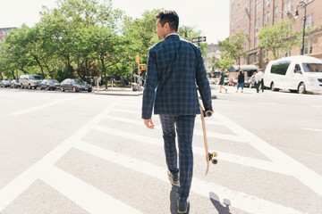 Rear view of suit wearing male skateboarder crossing road, West Village, Manhattan, USA