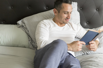 Mid adult man, relaxing on bed, reading book