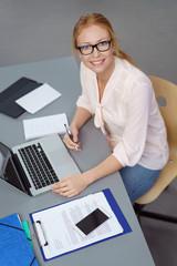 geschäftsfrau arbeitet am schreibtisch mit laptop und unterlagen