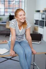 frau sitzt im büro auf dem schreibtisch und lacht