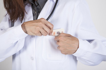 woman doctor hands with white gown and stethoscope tucking a wad of Euro banknotes in her pocket