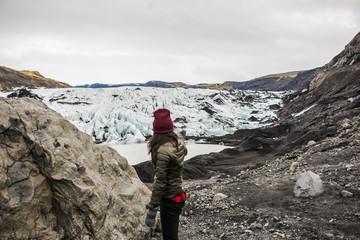 Female tourist pointing at glacier at Solheimajokull, Iceland