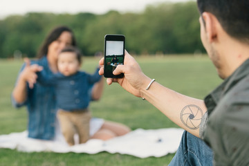 Young man using smartphone to take photograph of family