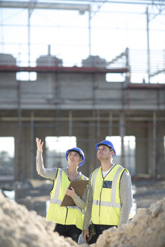 Surveyor looking up whilst talking to builder on construction site