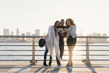 Three mid adult friends taking smartphone selfie on waterfront, New York, USA