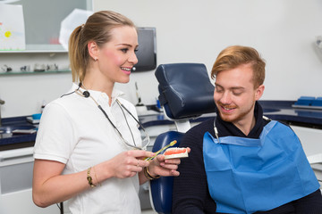 Dentist advising a patient about cleaning teeth properly