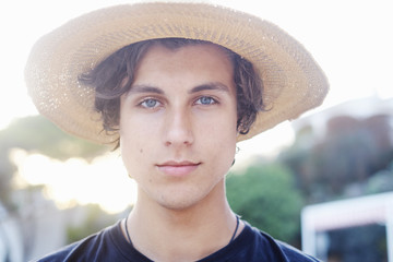 Close up portrait of young man wearing sunhat at beach