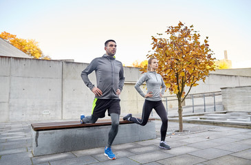 couple doing lunge exercise on city street