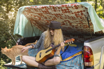 Young woman petting cat and playing ukulele whilst camping in pick up boot